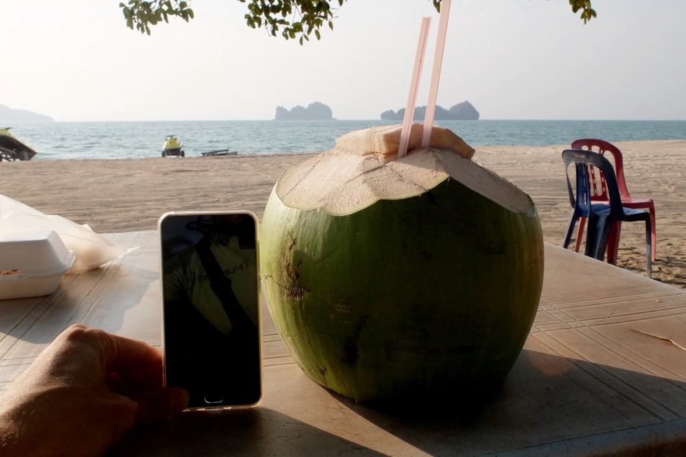 Drinking coconut water on Tanjung Rhu beach