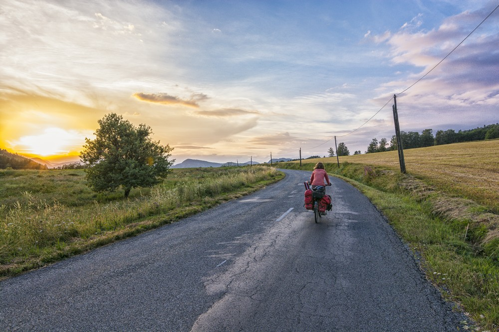 Cycling into the sunset in the Alps. Ilze. Cycling around the world.