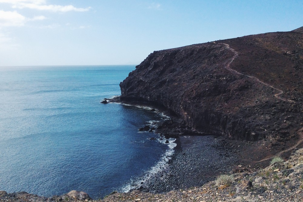 Wild beach surrounded by cliffs, black sand and rock beach - Fuerteventura, Canary islands