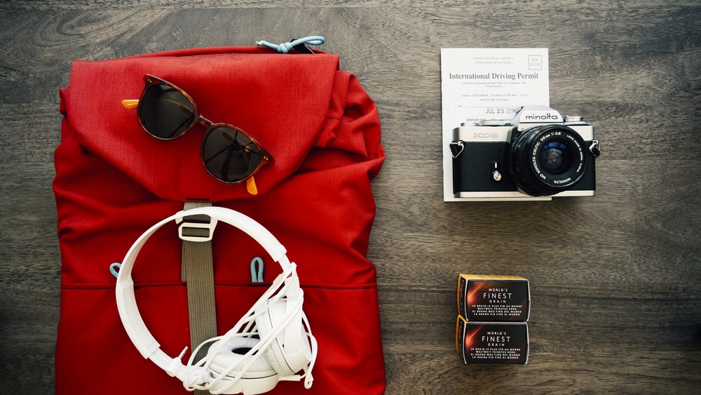 Photo of a backpack, camera and earphones