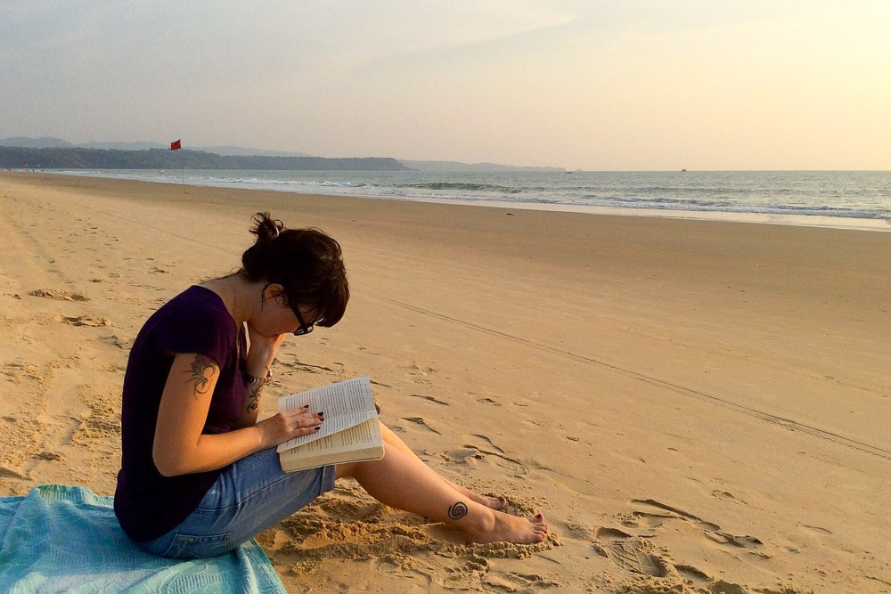 Girl reading a book on the beach in Goa - Best Travel Towels