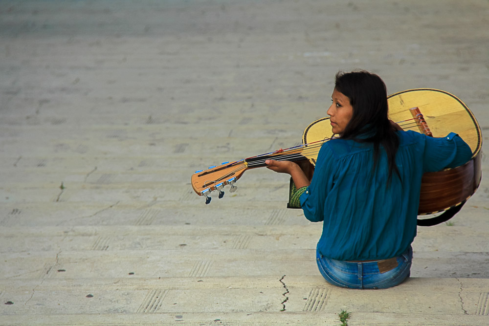 Woman playing guitar - Nomadic Traveler Ray Gudrups