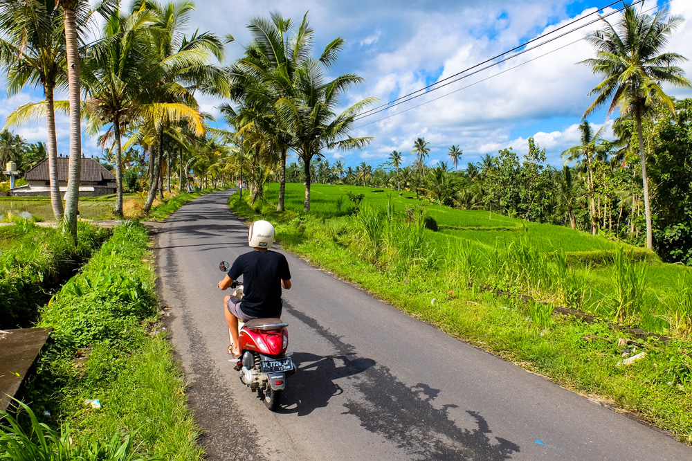 Driving a scooter on a narrow road in Bali, Indonesia