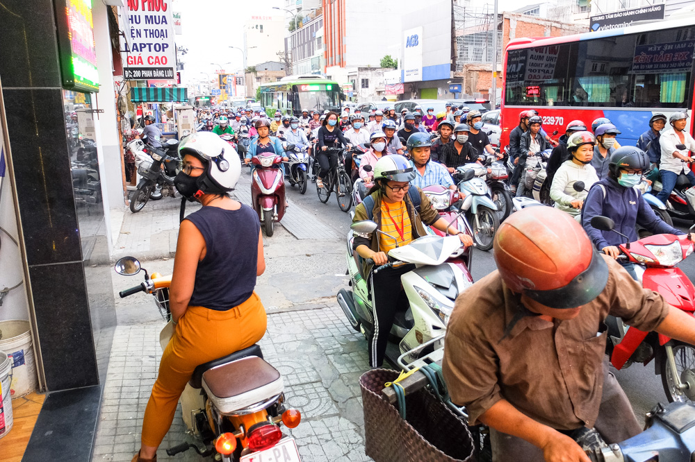 A woman on a scooter standing on a sidewalk in Ho Chi Minh City - Vietnam Photo Story