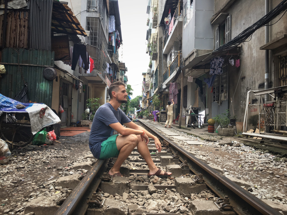 Adrian in Hanoi, sitting on the railroad tracks - Interview with Digital Nomad Adrian Sameli