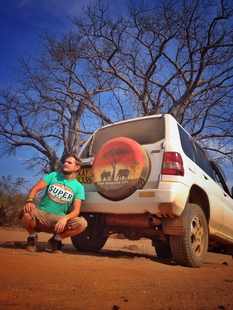 Adrian in Zambia sitting next to a car - Interview with Digital Nomad Adrian Sameli