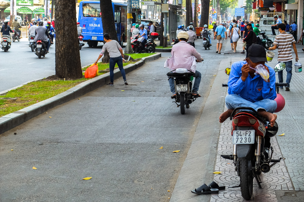 Man eating while sitting on a scooter in Ho Chi Minh City - Vietnam Photo Story