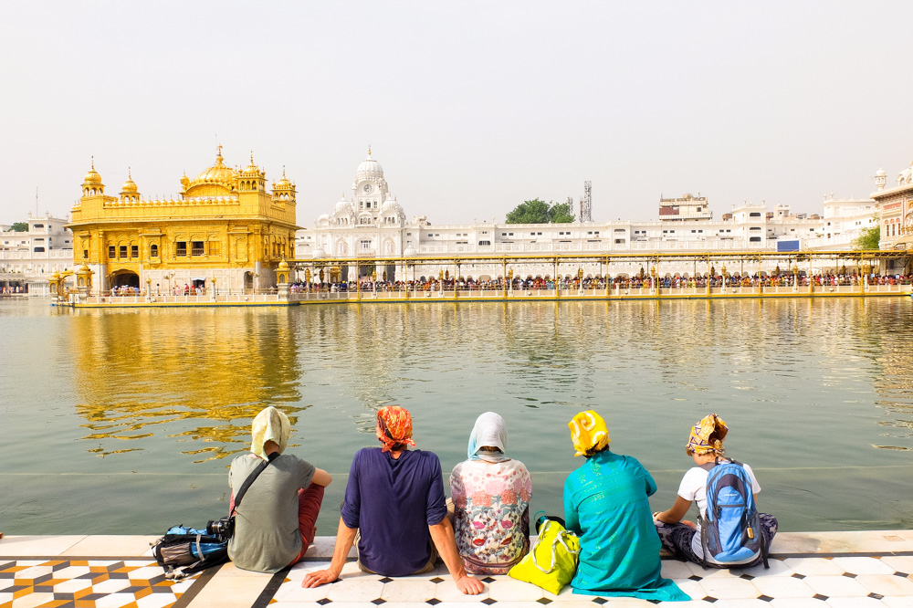 Tourists sitting and looking at The Golden Temple - Amritsar, India
